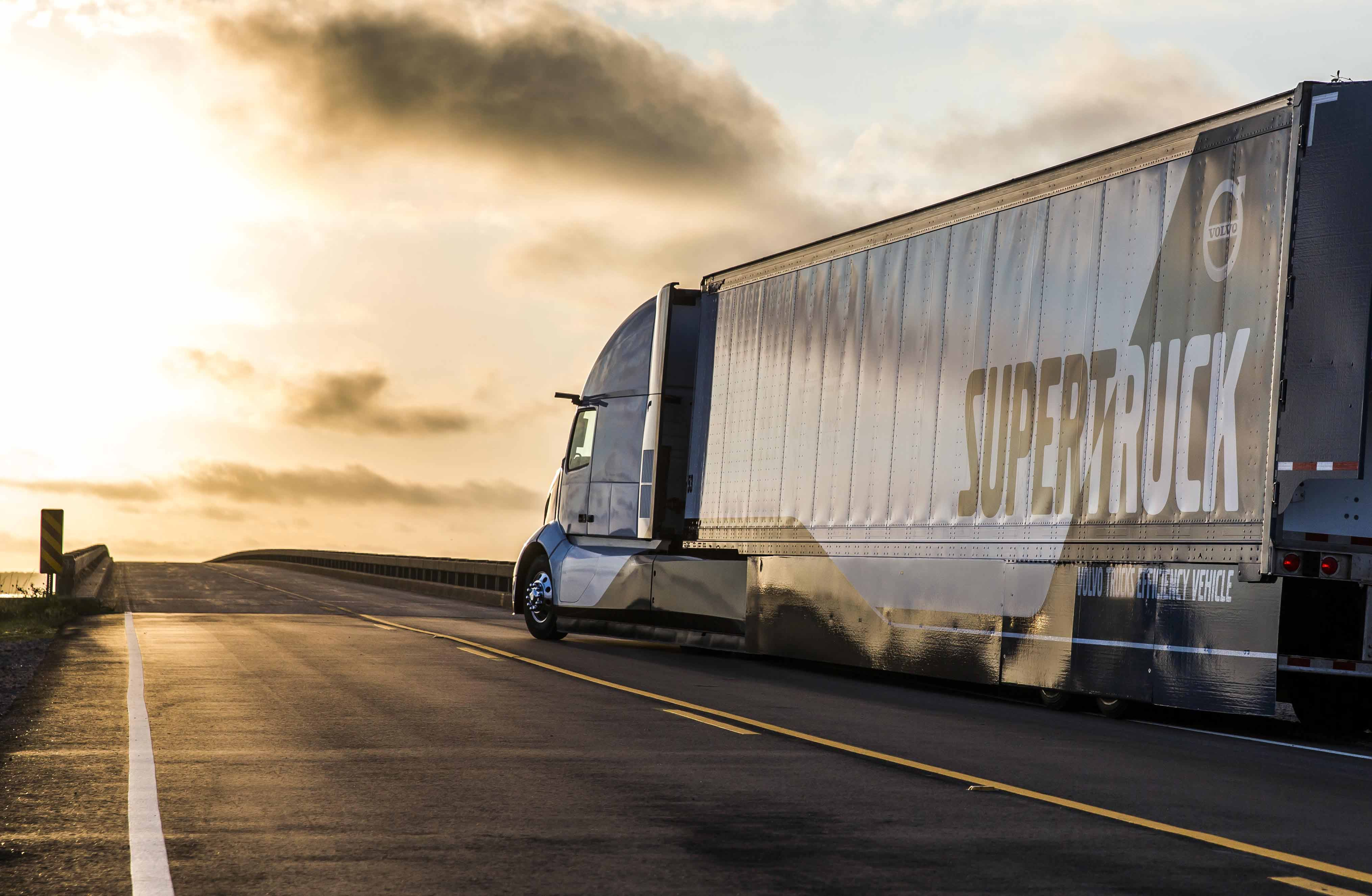 perspective view of Volvo SuperTruck driving on a highway with a sunset on the background